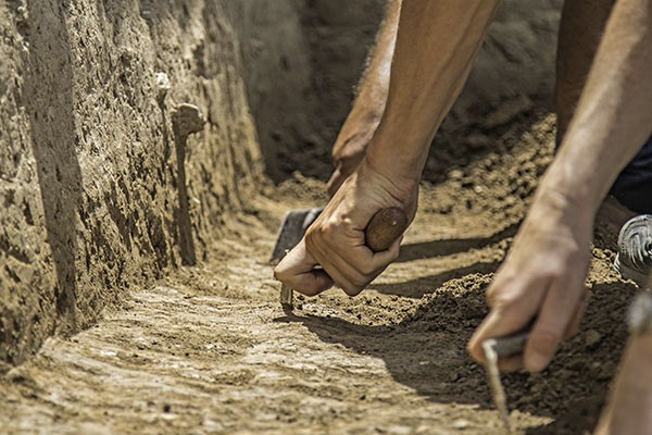 Trowelling hands in a trench.
